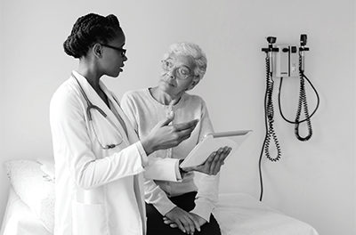 Picture of african femal doctor talking with elderly patient