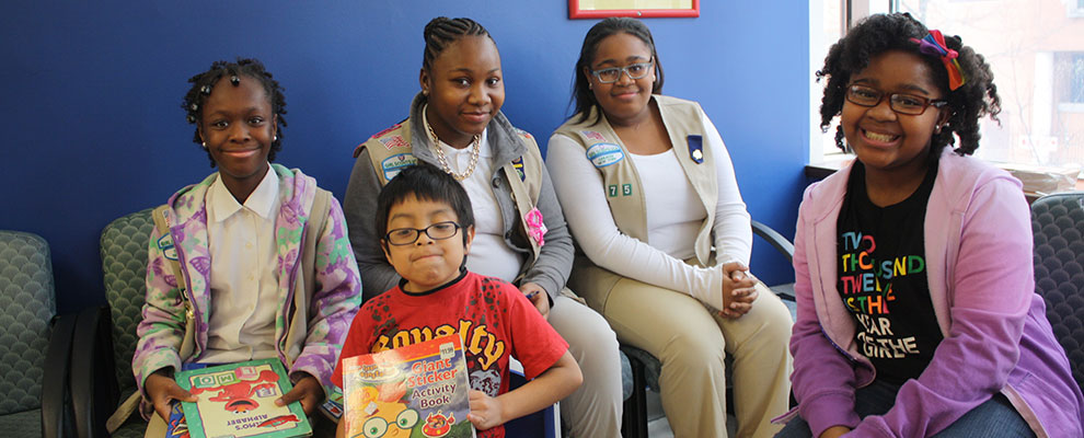 Image of Girl Scouts Reading books to kids