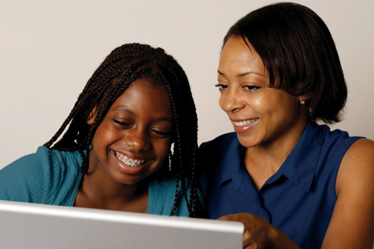 Image of mom and daughter looking at computer talking about how to spot a troubled teen