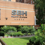 Image of SBH Health Sytem exterior, announcing Dr. David Perlstein as new President and CEO