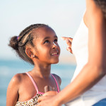 Image of mother applying sunscreen on child at the beach