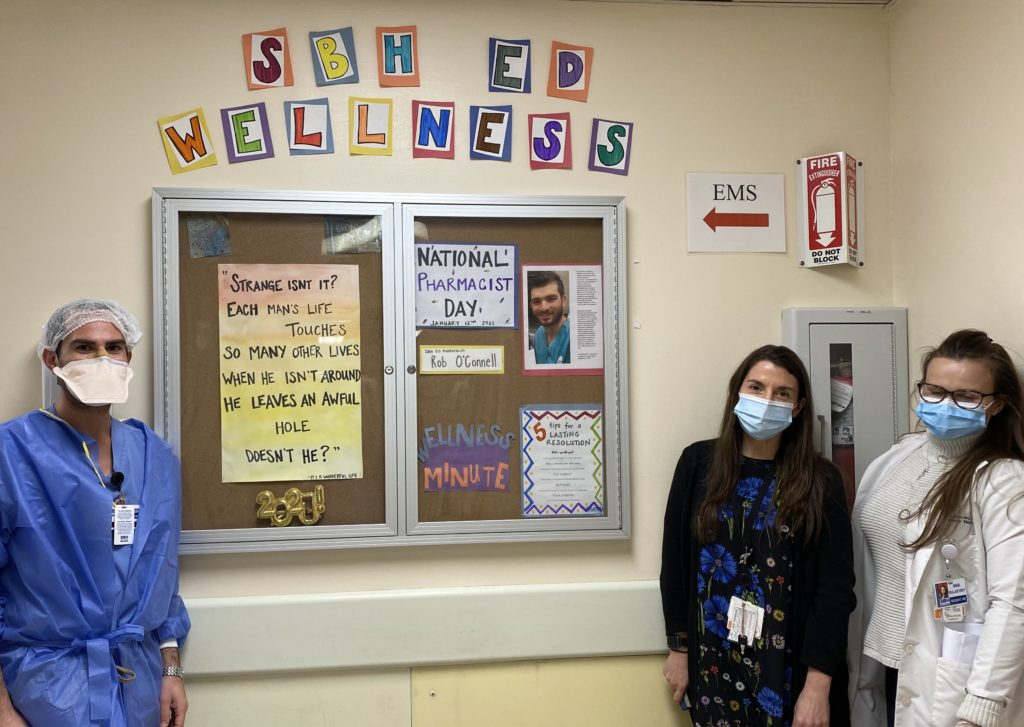Picture of SBH EM Residents next to an ED wellness bulletin board