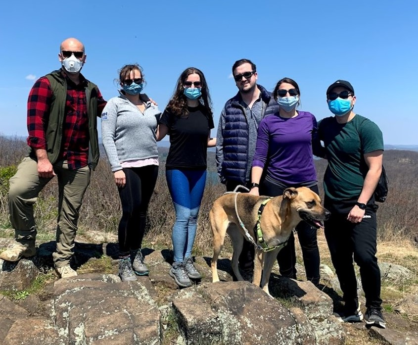 Picture of SBH EM Residents on a rocky hill with a dog.