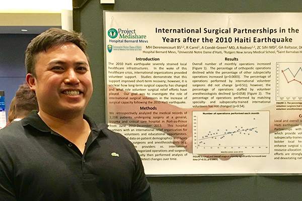 image of Gerard A. Baltazar DO FACOS in front of the scientific poster