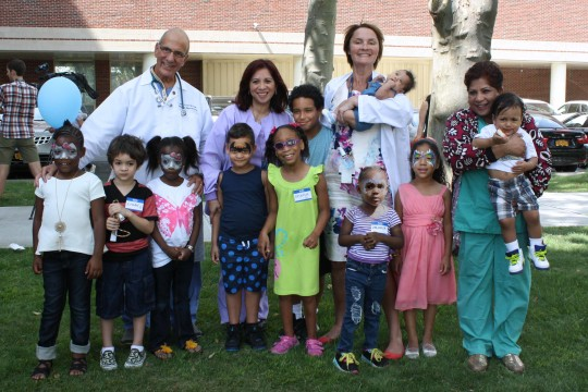 Image of Dr. Lezcano and his staff with ten children from the SBH NICU